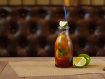 Освежая коктеиль с кусками лимона, зеленой известки и листьев мяты на запачканной деревянной предпосылке Стоковые Фото