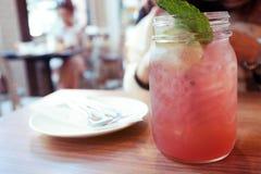 Освежение лета выпивает, стекло a замороженной соды клубники покрытой с листьями мяты помещено на деревянном столе Стоковое Изображение RF