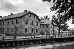 ОСВЕНЦИМ, ПОЛЬША - 11-ое июля 2017 Казармы и колючая проволока в a Стоковое Изображение