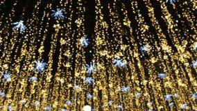 Освещение праздников рождества и Нового Года на открытом воздухе в улице города вечером Золотые мерцающие и развевая гирлянды акции видеоматериалы