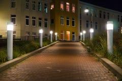 Освещенная дорога с фонариками в ландшафте города с домами на предпосылке стоковое изображение