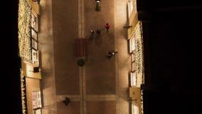 Освещенная узкая улочка с загоренными желтыми зданиями магазина и идя людьми акции видеоматериалы