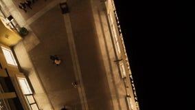 Освещенная узкая улочка с загоренными желтыми зданиями магазина и идя людьми сток-видео