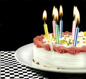 освещенные свечки именниного пирога Стоковые Изображения