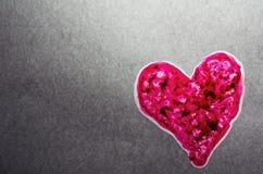 освещенный контржурным светом предпосылкой серый текстурированный пинк сердца Стоковые Изображения
