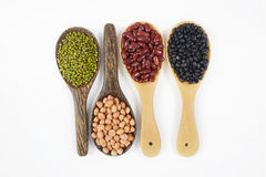 Осеменяет фасоль beansBlack, красную фасоль, арахис и фасоль Mung полезную для здоровья в деревянных ложках на белой предпосылке Стоковые Фото