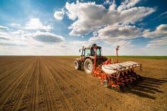 Осеменять фермера, засуя урожаи на поле стоковая фотография