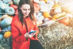 Осенний рынок тыквы Молодая женщина сидит и использует smartphone В предпосылке, сене и тыкве в мягком фокусе Стоковое Изображение