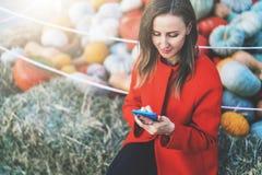 Осенний рынок тыквы Молодая женщина сидит и использует smartphone В предпосылке, сене и тыкве в мягком фокусе Стоковое фото RF