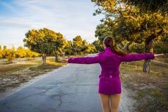 Осень в листьях, девушка идет в расстояние вдоль бульвара Девушка распространила ее руки в различных направлениях стоковое фото
