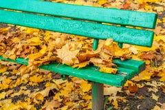 Осень край старой деревянной скамьи посыпан с упаденными листьями стоковая фотография rf