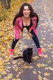 Осень, любимчики, концепция людей - счастливая женщина смеясь над с черным котом стоковая фотография