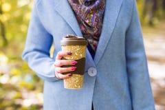 Осень, пить и концепция людей - чашка горячего питья в руке ` s женщины стоковые фото