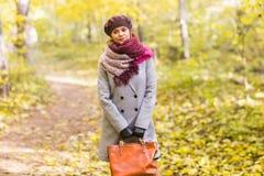 Осень, природа, концепция людей - красивая молодая женщина в сером пальто и берет стоя в парке стоковые изображения rf