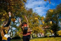 осень спелая 2 девушки студенты жизнерадостно тратят время в парке города Стоковое Фото