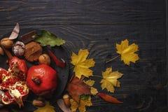 осень яблока миражирует листья состава сухие sacking ваза Гранатовое дерево с гайками, специями и сухими листьями на темном дерев стоковые фотографии rf