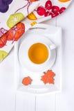 осень яблока миражирует листья состава сухие sacking ваза Травяной чай и пряник в форме кленового листа и жолудя на белой деревян Стоковые Фото