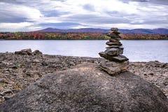 Осень Inukshuk на утесе около спокойного озера на облачном небе с Стоковая Фотография RF