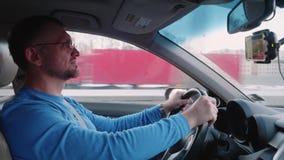 Ослабленный белый человек управляет автомобилем около города сток-видео