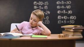 Ослабленный пробуренный школьник сидя на столе, неохотном для подготовки домашней работы математики сток-видео