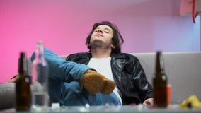 Ослабленный пьяный молодой человек сидя на софе, boozer наслаждаясь музыкой на танцах акции видеоматериалы