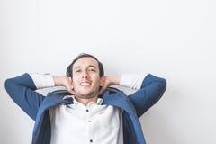 Ослаблять бизнесмена сидя на белой предпосылке Стоковые Фотографии RF