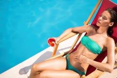 Ослаблять и солнце женщины загорая бассейном Стоковое Фото