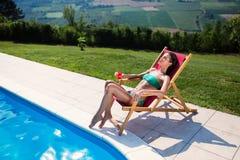 Ослаблять и солнце женщины загорая бассейном Стоковое фото RF