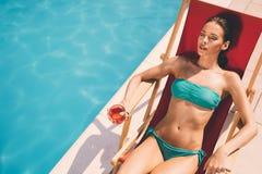Ослаблять и солнце женщины загорая бассейном Стоковые Изображения RF