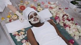 Ослаблять красивой молодой африканской женщины отдыхая в спа-курорте пока cosmetologist прикладывает лицевую маску на ее стороне  акции видеоматериалы