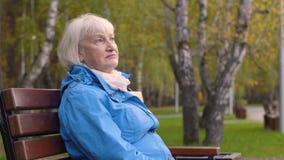 Ослаблять портрета более старый на стенде в парке осени и смотреть в sideway видеоматериал