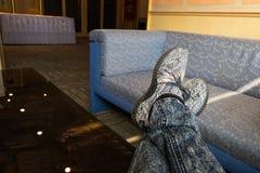 Ослаблять человека который пересекает его ноги пока носящ серый цвет стоковое фото