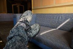 Ослаблять человека который пересекает его ноги пока носящ серый цвет стоковое изображение