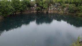 Ослабляя взгляд красивой албанской природы Светлый дождь падает в естественное озеро окруженное зеленой флорой сток-видео