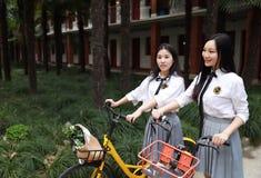Ослабьте азиатского китайского милого студента носки девушек костюм в школе наслаждается велосипедом езды свободного времени в са Стоковая Фотография RF