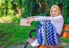Ослабьте даже немногие минуты уменьшите стресс Сада книги владением дамы день довольно счастливого солнечный Девушка сидит стенд  стоковое изображение rf