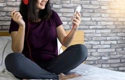 ослабьте женщину положите на кровать для того чтобы слушать музыку стоковые изображения rf