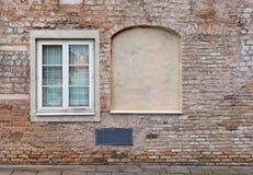 Ослепите изогнутые окна подвала в старом постаретом доме красных кирпичей стоковая фотография