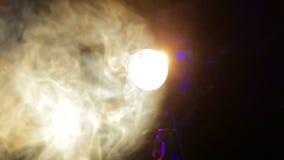 Ослеплять желтый луч театральной фары профиля в облаках дыма на этапе акции видеоматериалы
