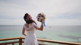 Ослепляя невеста наслаждается счастьем от высоты балкона обозревая океан и рифы Полет влюбленности экзотическо акции видеоматериалы
