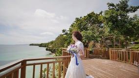 Ослепляя невеста наслаждается счастьем от высоты балкона обозревая океан и рифы Полет влюбленности экзотическо сток-видео