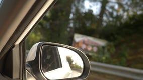 Осмотрите вне зеркало заднего вида, когда автомобиль проходит вдоль дороги летом 4k, стрельба замедления акции видеоматериалы