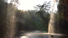 Осмотрите кафе формы под живописным водопадом в джунглях на времени вечера Вода падения в бассейн через лучи солнца на акции видеоматериалы