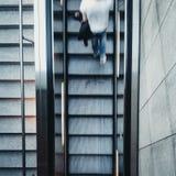 Осмотрите сверху на быстроподвижном молодом человеке идя вверх по лестницам эскалатора стоковое фото rf