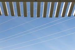 Осмотрите смотреть вверх через край перголы на голубом небе с линиями электропередач стоковые изображения rf