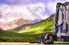 Оснащение для кемпинга, и рюкзак на предпосылке гор Стоковое фото RF