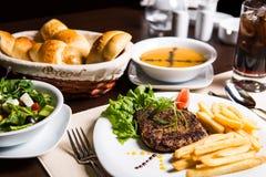 Основное блюдо, soupe, салат, хлеб и питье для обедающего Стоковые Изображения