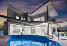 Особняк с бассейном и красивое небо на сумраке Стоковое фото RF