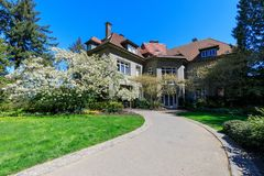 Особняк Pittock, взгляд на доме окруженном деревьями от сада на красивый солнечный весенний день, Портленда Стоковые Фотографии RF