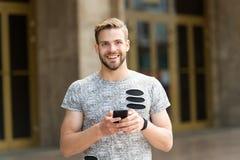 оставаться касанием Пошлите концепцию сообщения Человек с бородой идет с smartphone, городской предпосылкой Smartphone пользы Гая стоковое фото rf